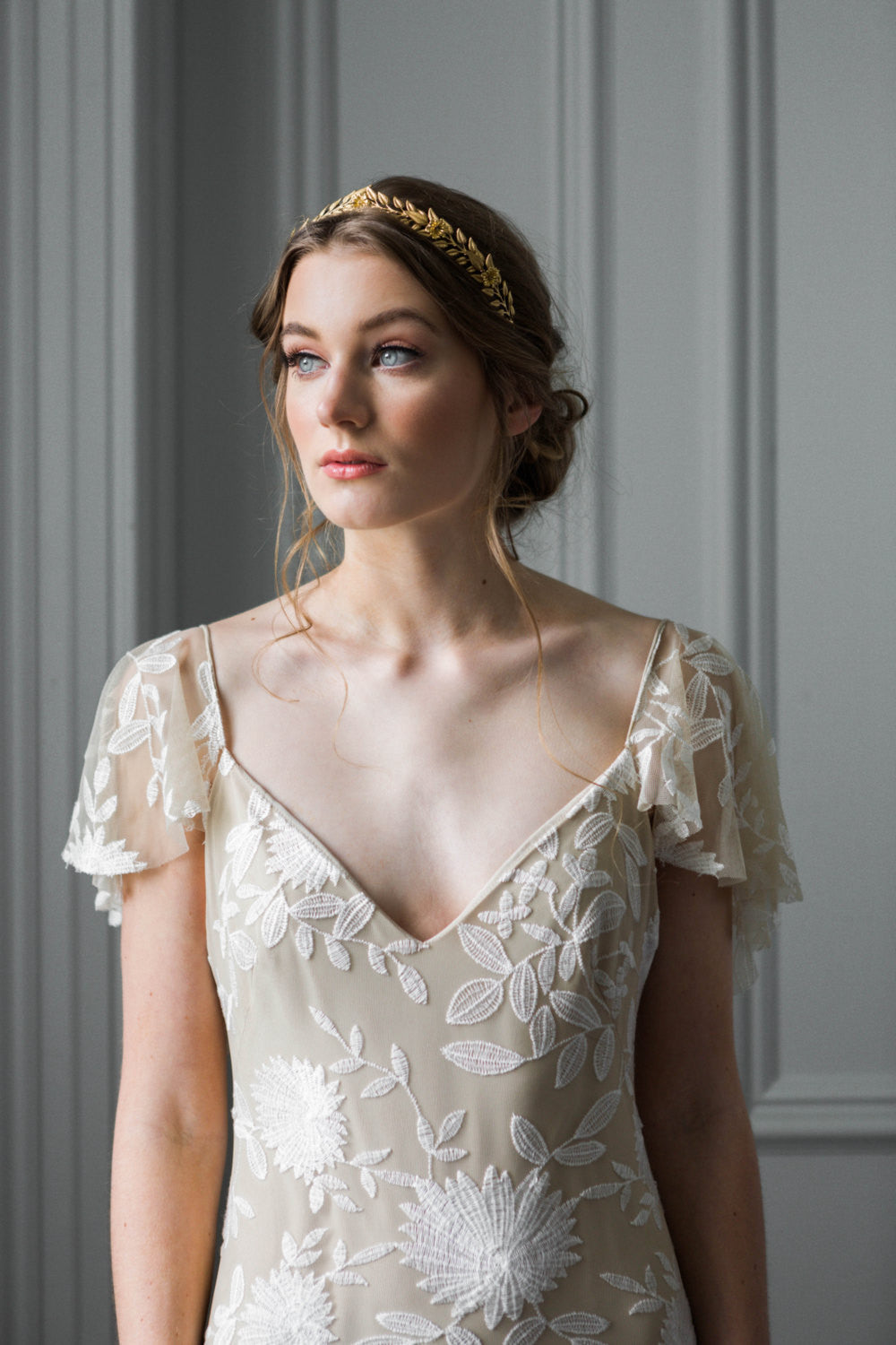 Model in a wedding dress wearing a gold Edwardian leaf bridal tiara