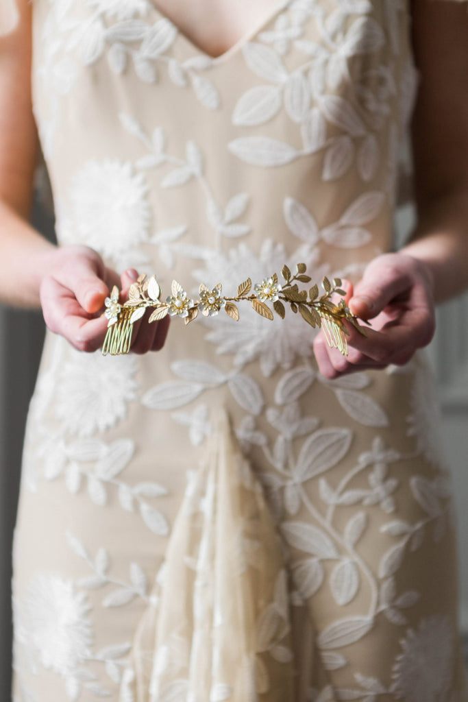 Bride holding bridal headpiece made of gold vines
