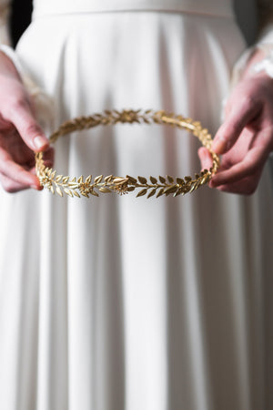 Bride holding a gold edwardian leaf circlet crown
