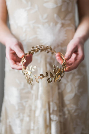 Model in white gown holding a gold laurel leaf bridal headpice
