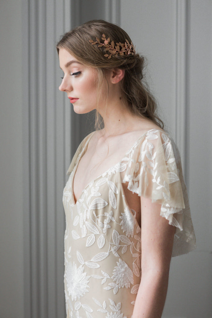 Model in a wedding dress wearing a gold leaf wrap headpiece