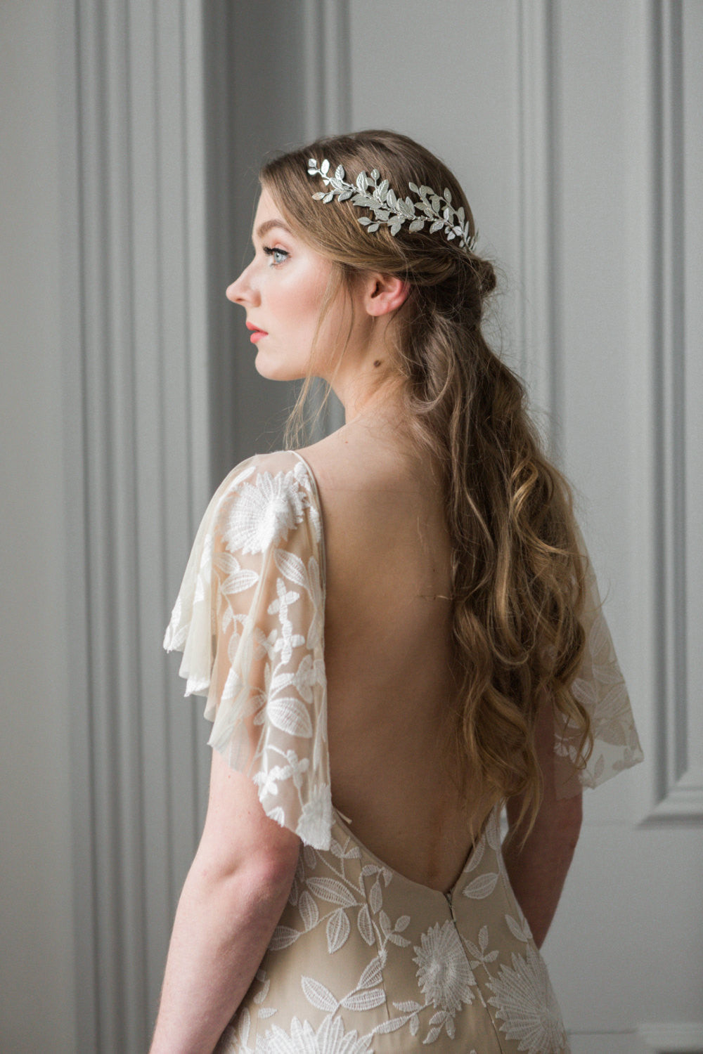 Model in wedding dress wearing a silver bridal headpiece