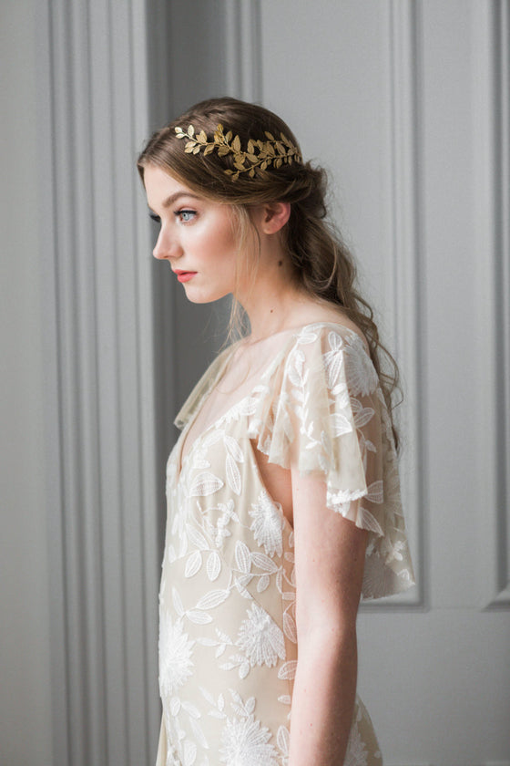 Model in white gown wearing a gold laurel leaf bridal heapiece wrapped around back of head