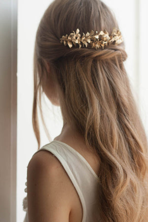 Model wearing a bridal headpiece made of gold myrtle leaves