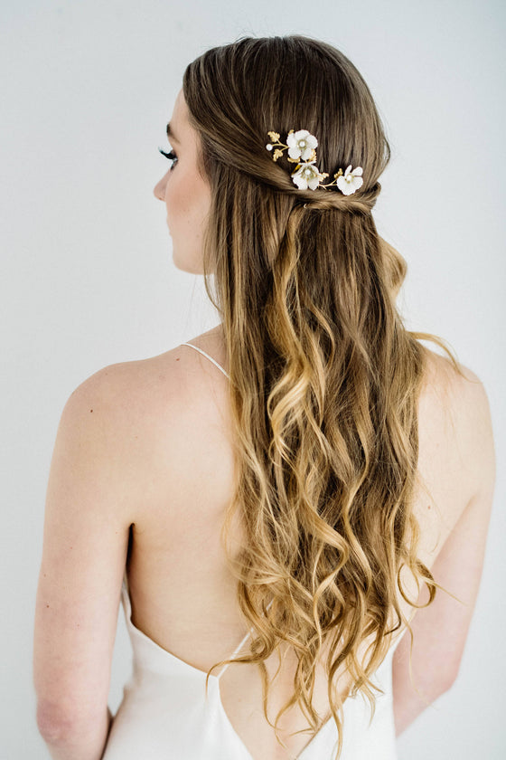 Bride wearing a hair comb made of gold leaves and ivory flowers