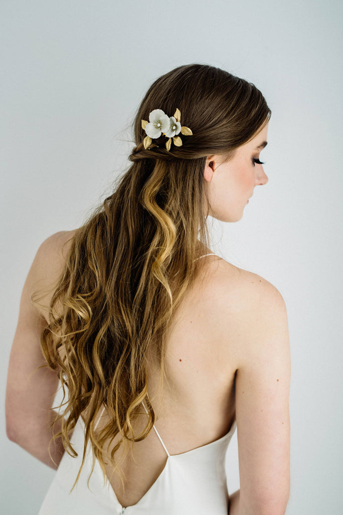 Bride wearing a bridal hair comb made of gold and ivory flowers