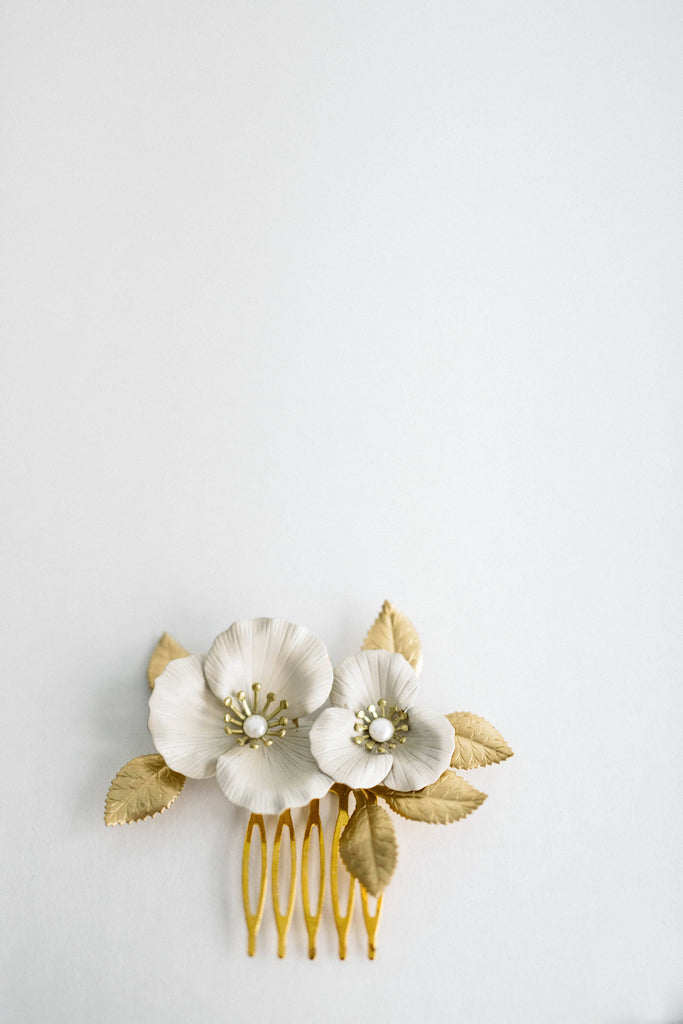 Close up of a hair comb made of gold and ivory flowers