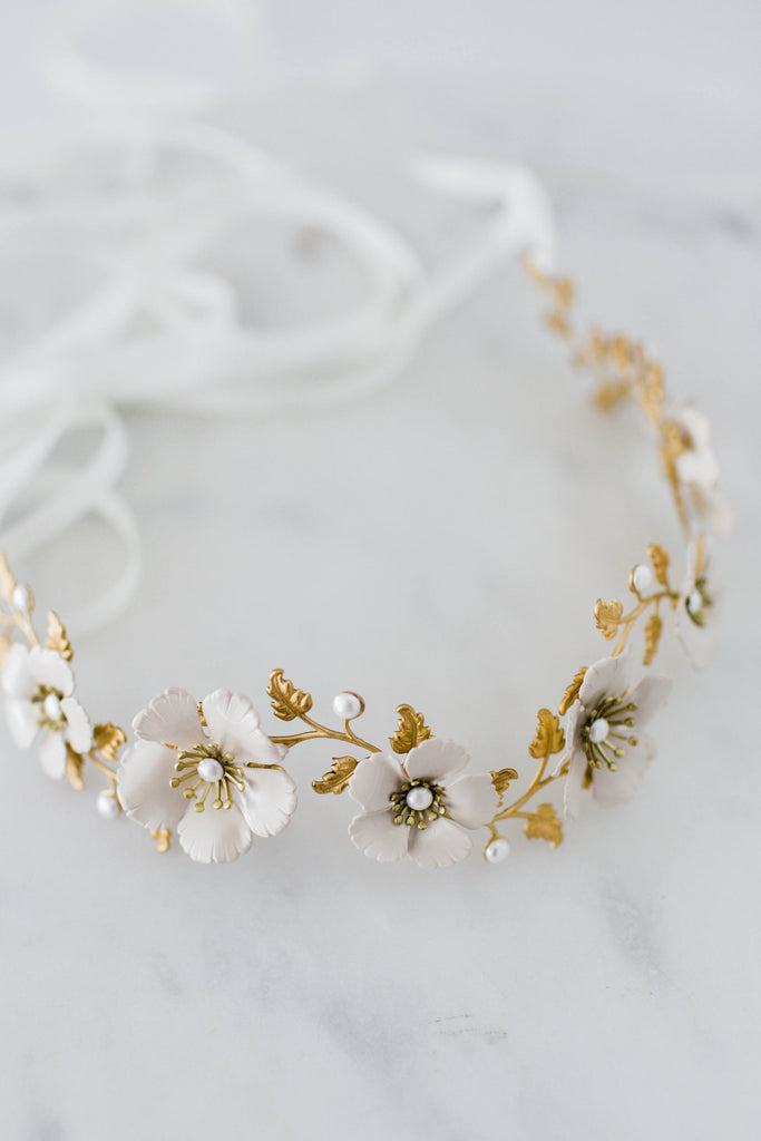 close up of a headpiece made of gold leaves and ivory flowers
