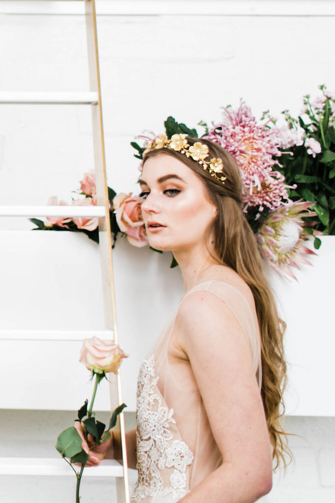 A bride wearing a tiara made of gold leaves and roses