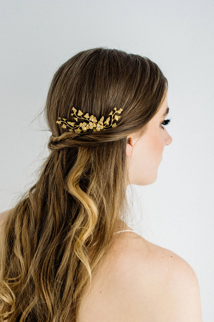 Model wearing a bridal headpiece made of gold leaves and flowers