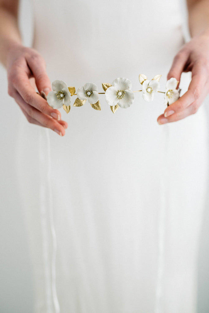 Model holding a bridal tiara made of gold and ivory flowers