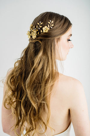 Model wearing a bridal headpiece made of gold leave and flowers