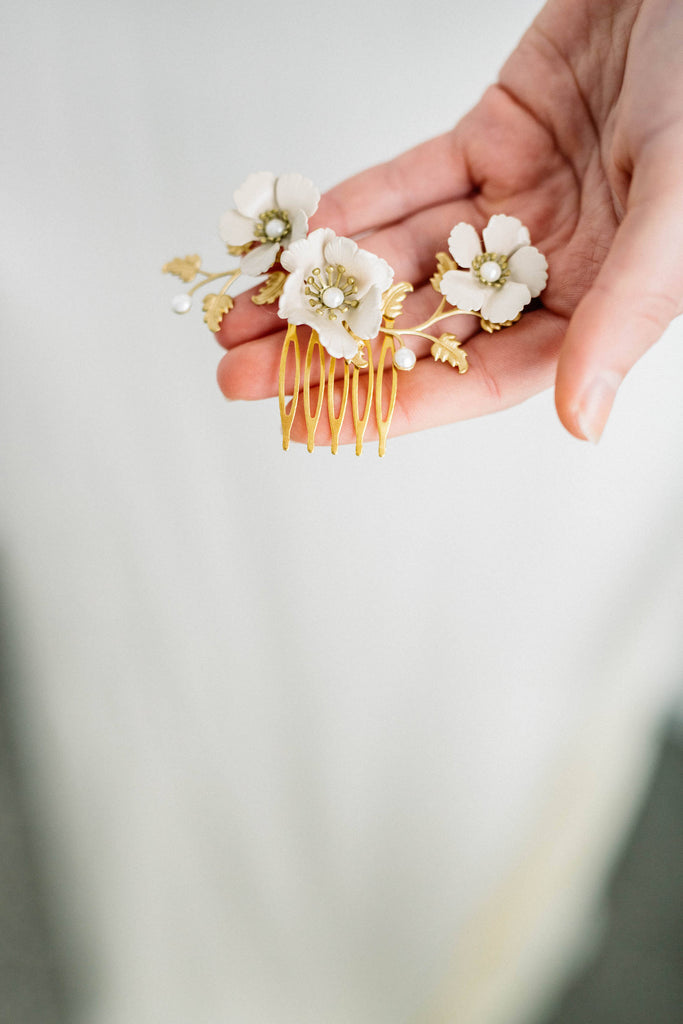 Close up of a hair comb made of gold leaves and ivory flowers