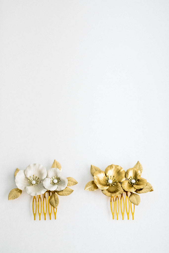 Close up of two bridal hair combs made of gold and ivory flowers