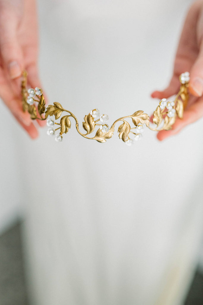 Model in wedding dress holding gold bridal tiara
