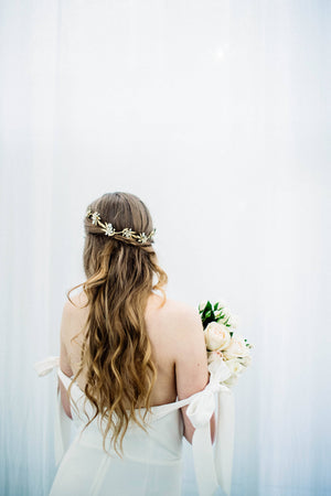 Model in wedding dress wearing a gold and crystal bridal tiara