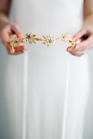Model in wedding dress holding a gold and crystal bridal tiara