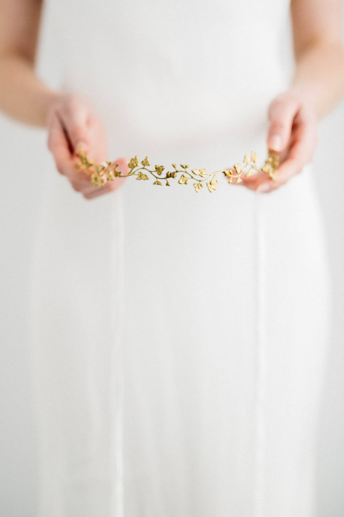 Model holding a bridal headpiece made of gold leaves and flowers