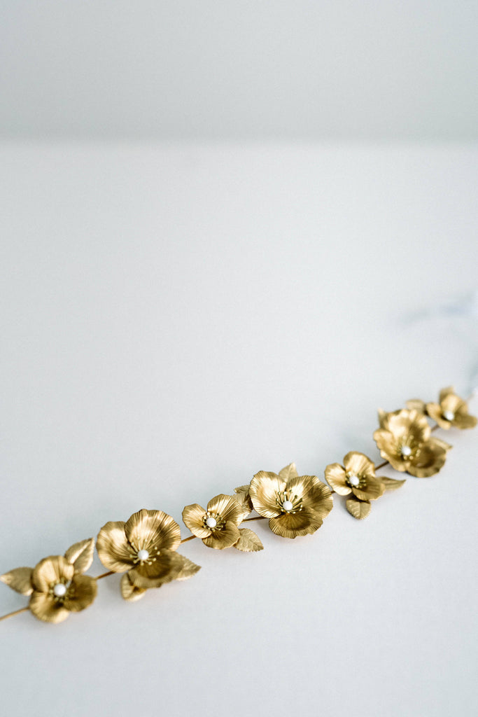 Close up of a bridal sash made of gold leaves and flowers