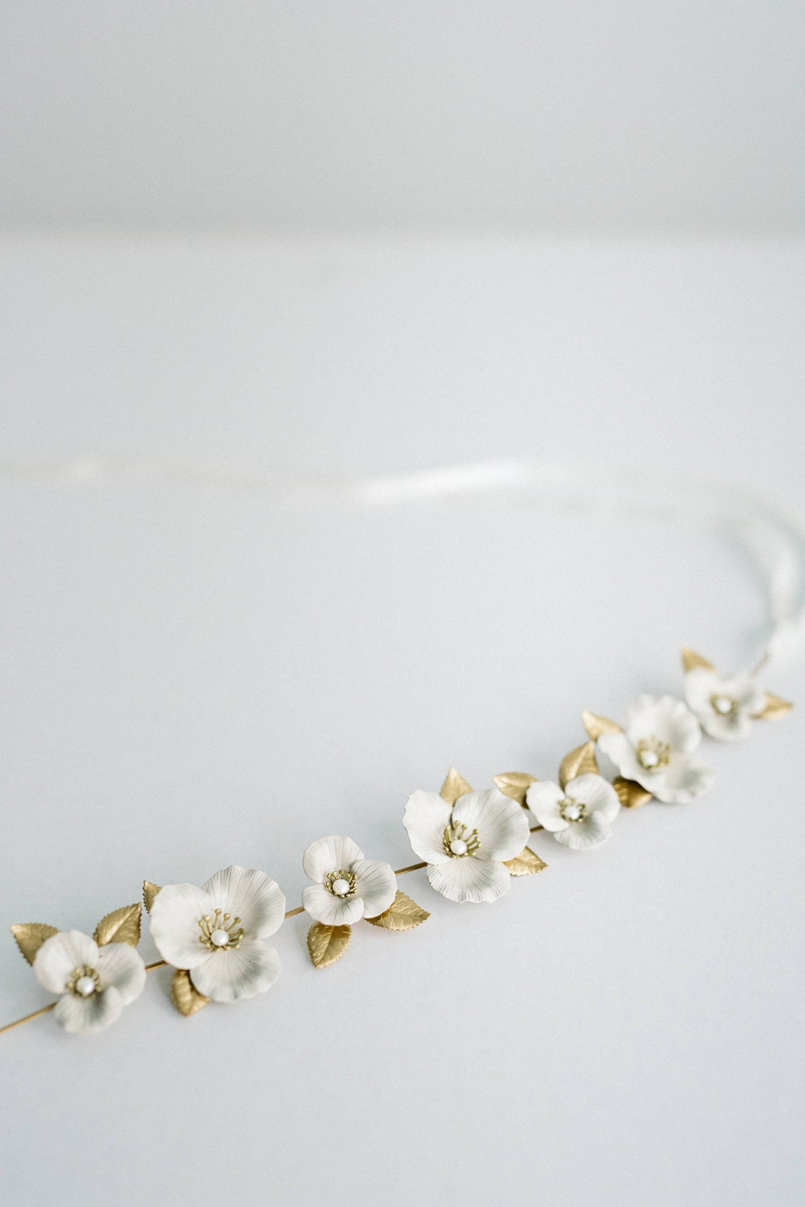 Close up of a bridal sash made of gold leaves and ivory flowers