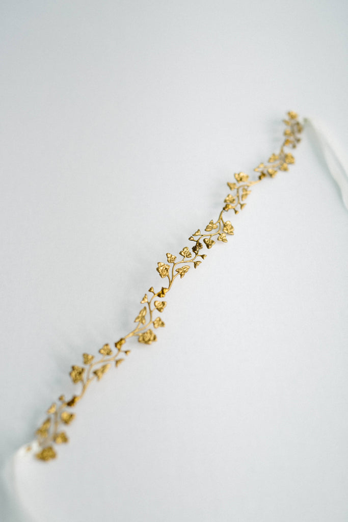 Close up of a bridal sash made of gold leaves