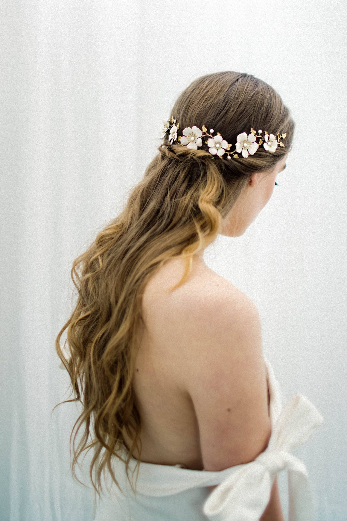 Bride wearing a wrap headpiece made of gold leaves and ivory flowers