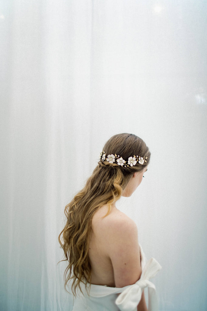 model wearing a bridal headpiece made of gold and ivory flowers