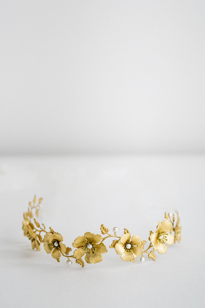 close up of a bridal headpiece made of gold flowers