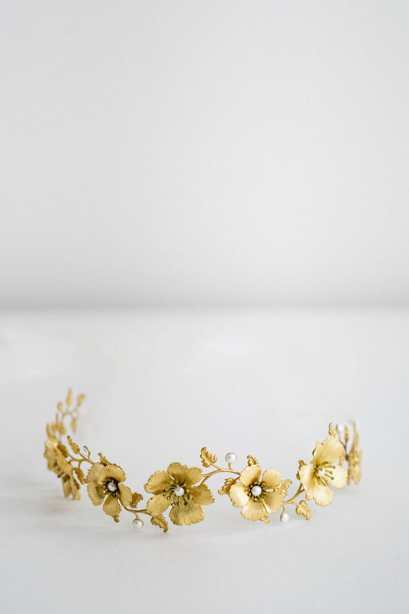 model wearing a bridal headpiece made of gold flowers