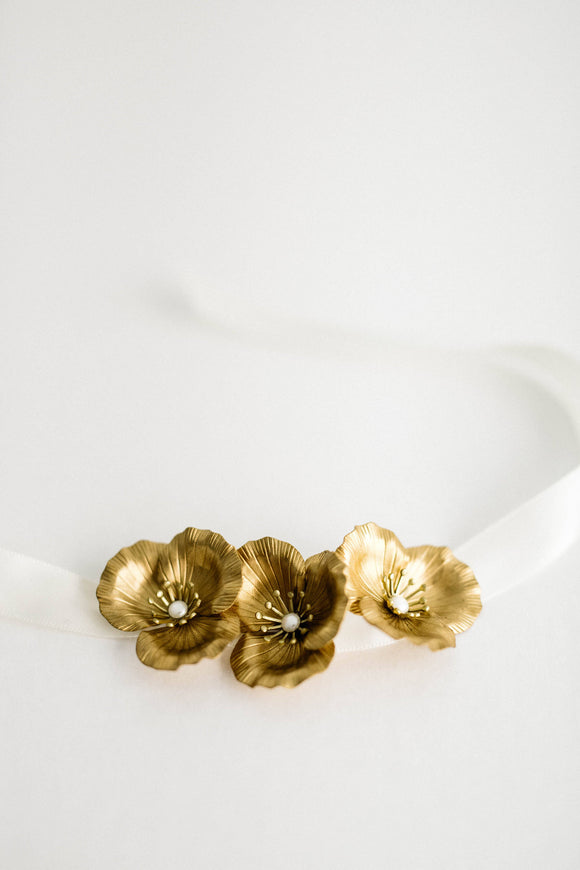 Bride wearing a bracelet made of three gold flowers