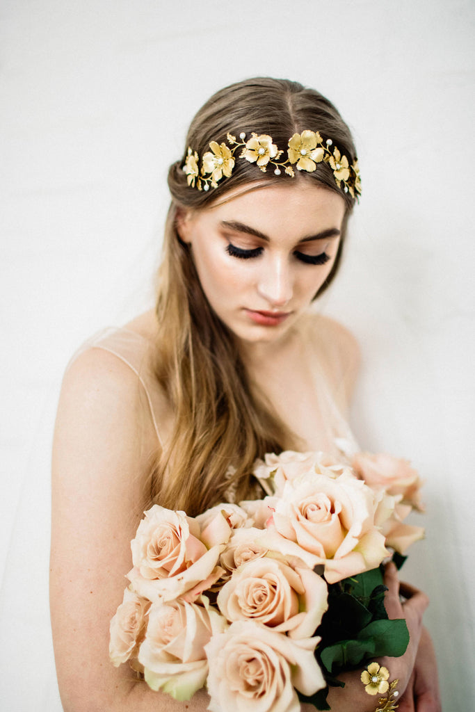 Bride wearing a headpiece made of gold flowers and leaves