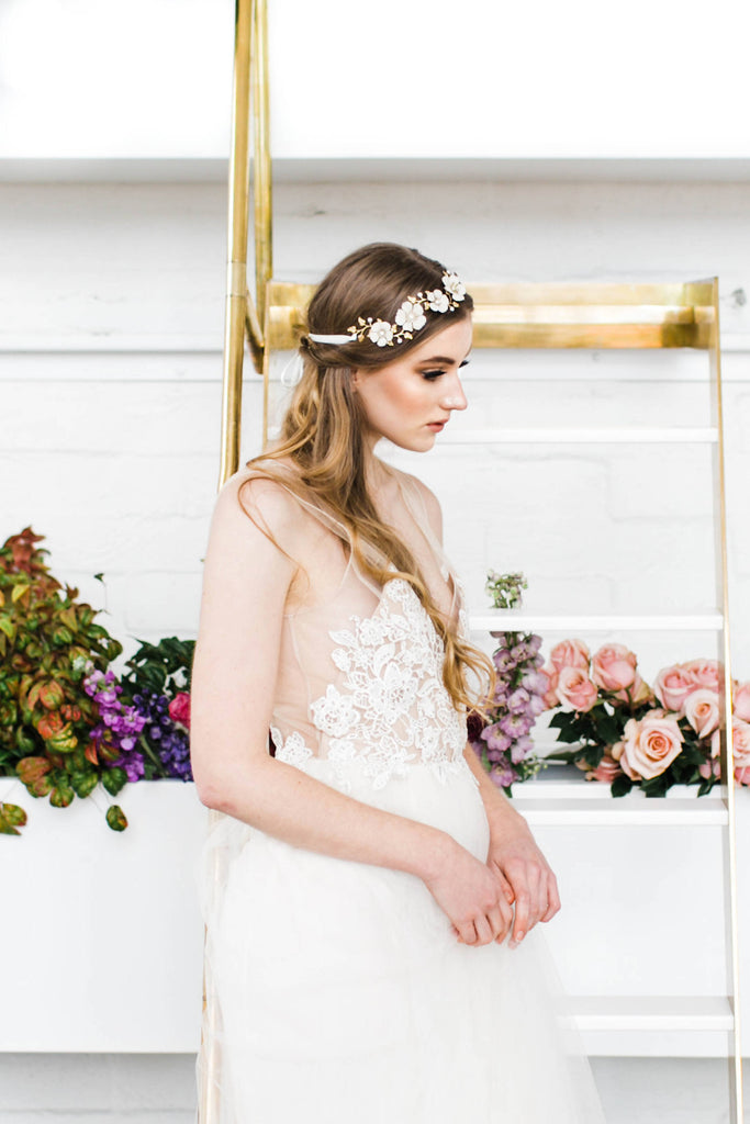a bride wearing a headpiece made of gold leaves and ivory flowers