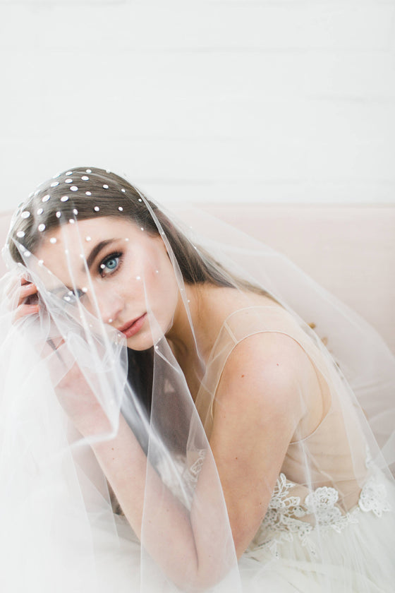 Bride wearing a veil covered in pearls