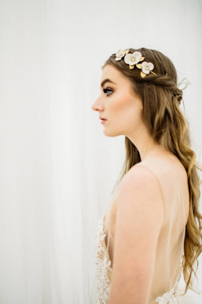 model wearing a bridal tiara made of gold and ivory flowers