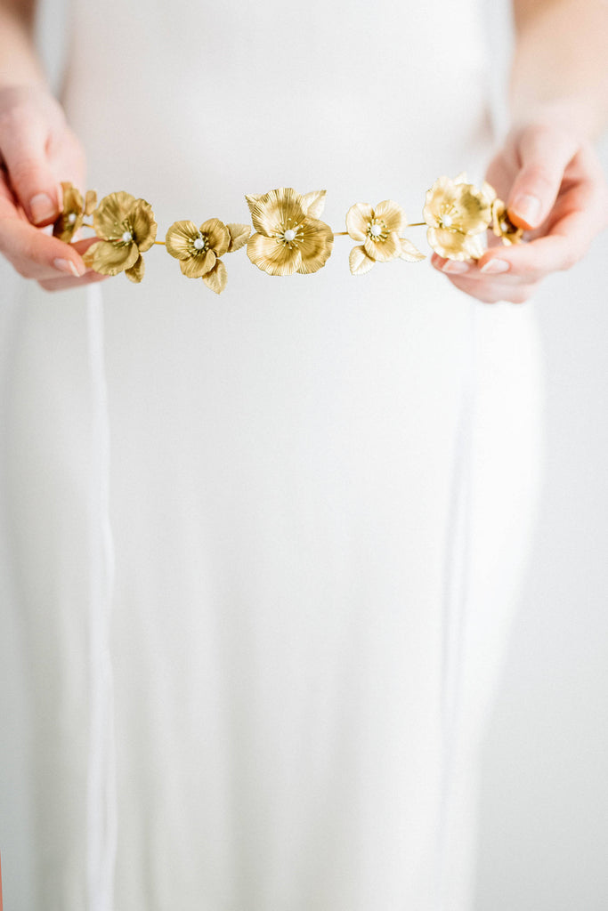 Model holding a bridal tiara made of gold flowers