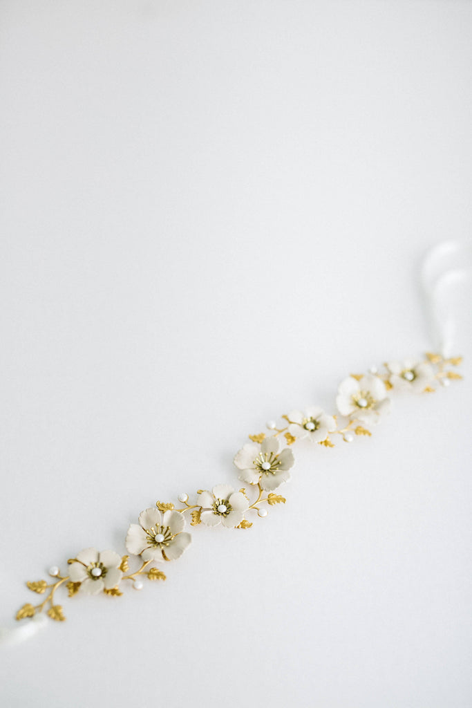 Close up of a sash made of gold leaves and ivory flowers