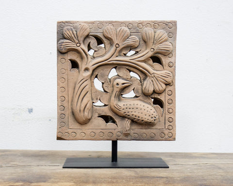 Antique brick with bird in a pine tree
