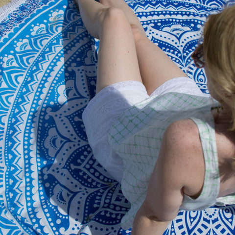 White hand embroidered beach shorts and blue roundie beach towel