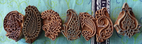 Row of small indian hand block stamps in the shapes of various traditional paisley and booti designs