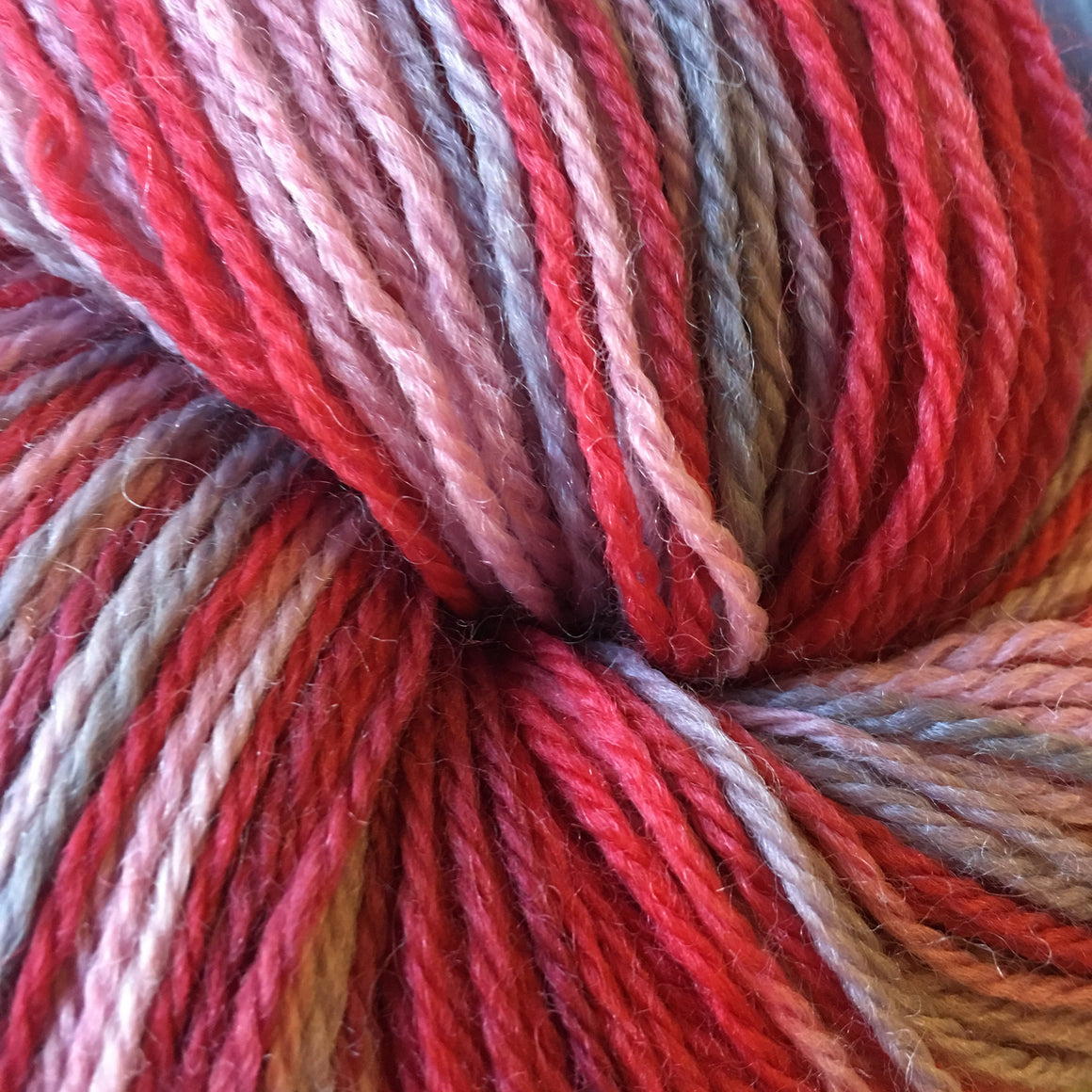 """February Love"" is a valentine red pink and gray variegated yarn on super wash merino fingering weight yarn"
