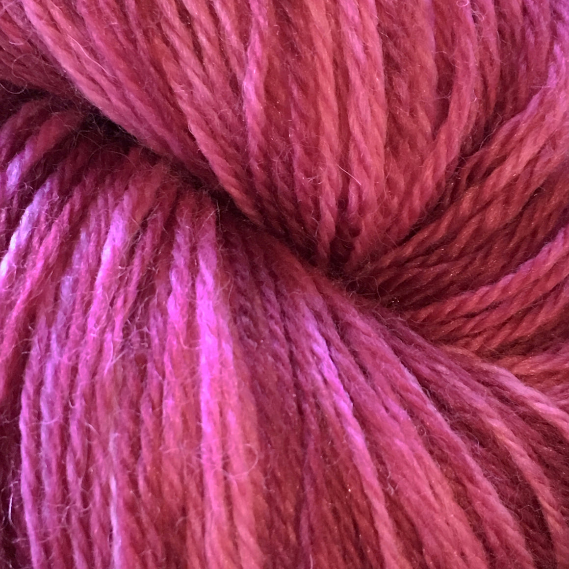 """Tiny Dancer"" has deep purple and magenta tones on a bright pink background in this fingering weight super wash merino/nylon blend yarn"