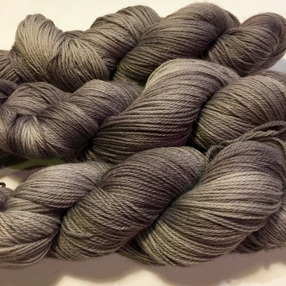 """Thunderstorm"" is deep gray tones on a fingering weight super wash merino yarn"