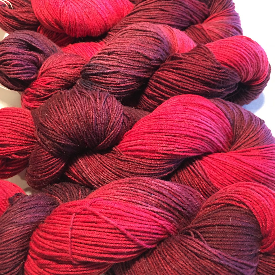 """Firestorm"" fingering weight bison yarn is multiple tones of reds and pinks"