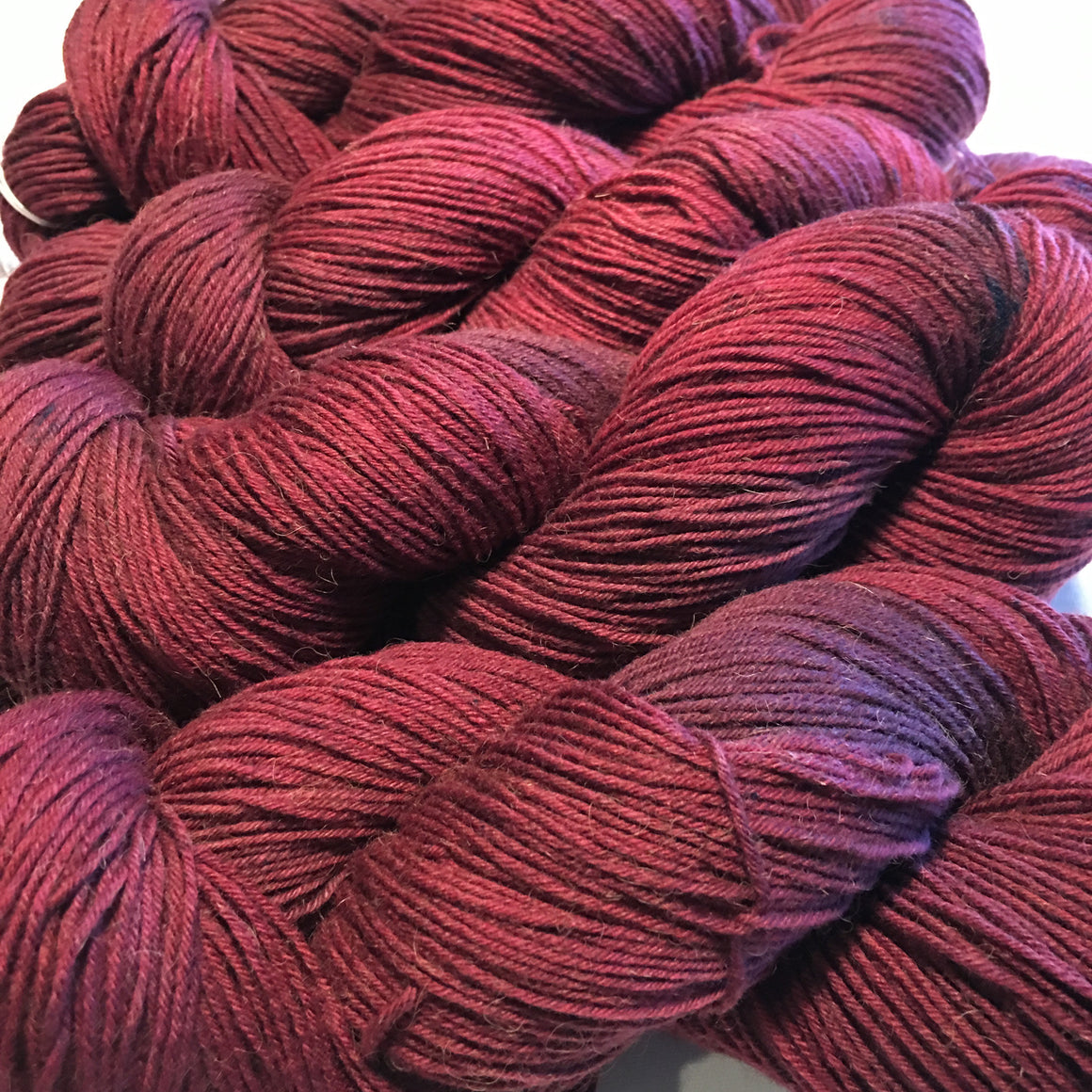"""Red Cliffs"" is a red toned blend in fingering weight bison blend yarn"