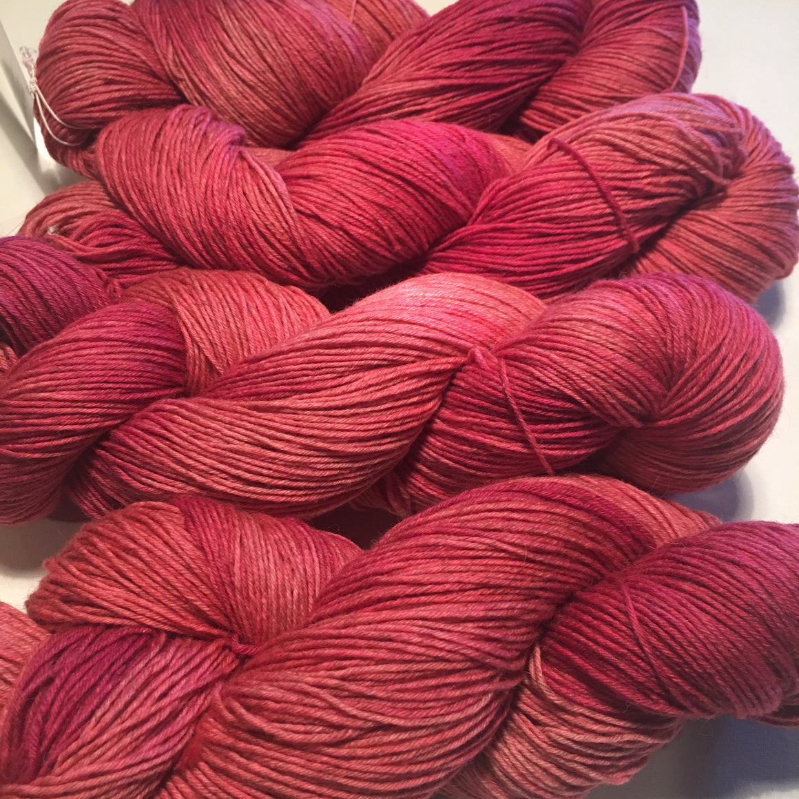 """Tippling Pink"" is a mixture of pink tones that burst from the bison blend fingering weight yarn"