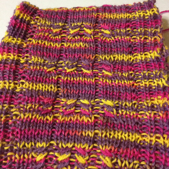 The Not a Sock Scarf is created with one skein of Knitting Rose Blossom Sock yarn. Blossom Sock yarn is a superwash wool and nylon blend in a fingering weight yarn. This scarf is designed by the Knitting Rose, Lise Wilson.