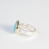 bright small turquoise gemstone ring set in 9ct gold with silver ring - left side
