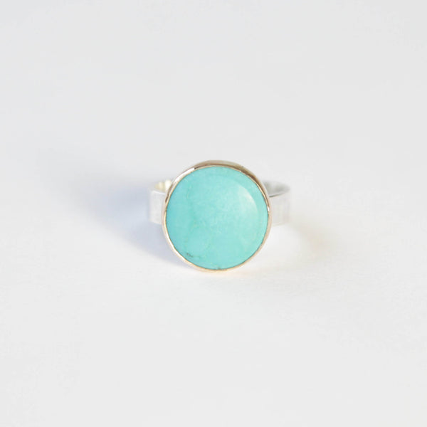 bright small turquoise gemstone ring set in 9ct gold with silver ring
