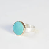 bright small turquoise gemstone ring set in 9ct gold with silver ring - front left