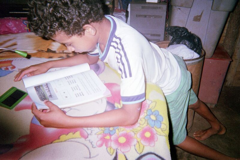 little boy studying using solar powered lamp donated by Esperanza Market